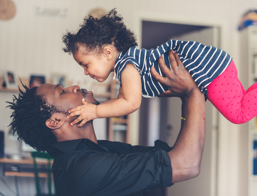 Man lifting his baby daughter in the air